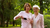 yaşlanma : senior women taking selfie by smartphone at park