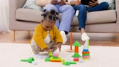 развивать : african baby girl playing with toy blocks at home