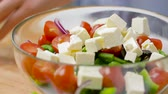 feta : woman cooking vegetable salad with feta and spices