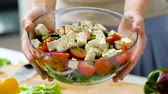 feta : woman holding bowl of vegetable salad with feta