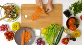 vegetarianismo : woman chopping carrot with kitchen knife at home