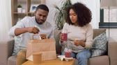 fogyasztás : couple with takeaway food and straw drinks at home Stock mozgókép