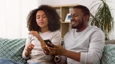 dallam : happy couple with smartphone and earphones at home Stock mozgókép