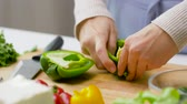 vegetarianism : woman cutting pepper in half and removing seeds Stock Footage