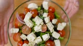 coalhada : hands turning bowl of vegetable salad with feta Stock Footage