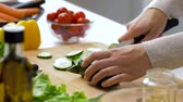 vegetarianismo : woman chopping cucumber with kitchen knife at home Vídeos