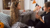 lampart : girls in halloween costumes playing game at home
