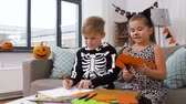 çita : kids in halloween costumes doing crafts at home