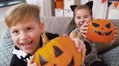 çita : kids in halloween costumes with pumpkins at home