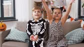 çita : kids in halloween costumes throw candies at home