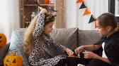 sopa : girls in halloween costumes with candies at home