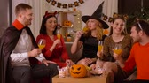 alkoholik : happy friends in halloween costumes at home party