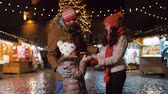 estonya : happy family with gift at christmas market in city