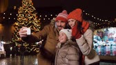 estonya : happy family taking selfie at christmas market