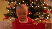baby girl sitting in gift box over christmas tree
