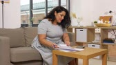sayma : woman with papers and calculator at home