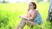 book : Happy young woman reads the book and contemplation at nature Stock Footage