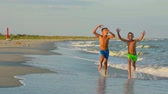 brother : Two happy  children run on the seashore at sunset.