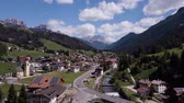 山頂 : Aerial shot of traditional swiss village in Switzerland on a sunny day. Summer scenery of small town with view of houses on green grassy hills,majestic mountains in background under clear blue sky 動画素材