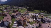 lagos : Aerial shot of traditional swiss village in Switzerland on a sunny day. Summer scenery of small town with view of houses on green grassy hills,majestic mountains in background under clear blue sky Stock Footage