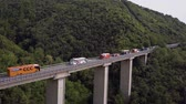 emilia : Aerial Italy. A big long bridge in a mountain valley. A lot of bike buses cost