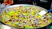 denominou : large pot of spanish seafood named paella cooking at public food market, typical food of a part of spain, healthy and nutrition concept