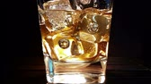 likör : barman pouring whiskey in the glass with ice cubes on wood table and black dark background, focus on ice cubes, whisky relax time on warm atmosphere Stok Video