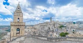 типичный : panoramic view of typical stones (Sassi di Matera) and church of Matera European Capital of Culture 2019 under blue sky white clouds time lapse movement, Basilicata, Italy