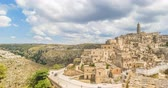 типичный : panoramic view of typical stones (Sassi di Matera) and church of Matera UNESCO European Capital of Culture 2019 under blue sky white clouds time lapse movement, Basilicata, Italy