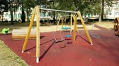 recessão : empty swings with chains for children, moved from wind, shot in slow
