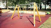 recessão : empty swings with chains swaying at playground for child, moved from wind, shot in slow