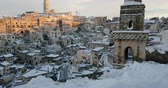 panoramic view of typical stones Sassi di Matera and church of Matera 2019 with snow on the house, concept of travel and christmas holiday on snowflakes at sunset, capital culture of europe 2019, Stock Footage