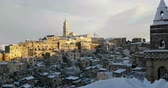 panoramic view of typical stones Sassi of Matera and church of Matera 2019 with snow on the house, concept of travel and christmas on snowflakes at sunset, capital culture of europe 2019,