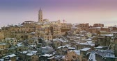 history : panoramic view of typical stones Sassi of Matera and church of Matera 2019 with snow on the house, concept of travel and christmas on snowflakes at sunset, capital culture of europe 2019,