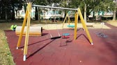 empty swings with chains for children, moved from wind, shot in slow