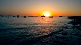sea wave calm at sunset with sun and boats in horizon, concept of relax and travel of nature and