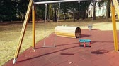 empty swings with chains swaying at playground for child, moved from wind, shot in slow