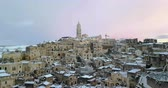 panoramic view of typical stones Sassi di Matera and church of Matera 2019 with snow on the house, concept of travel and christmas holiday on snowflakes at sunset, capital culture of europe 2019, Wideo