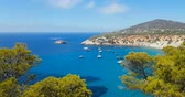 Famous, beautiful beach at daylight with calm sea, in summer very popular, sandy coast have a fantastic view of island of ibiza. Moored vessels on bay. Ibiza Island, Balearic Islands. Vídeos