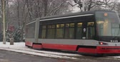 cz : Winter public transport in Prague in the winter on a snowy day. A tram and a train passing by each other. Slow motion