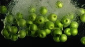 gravitace : Slow motion shot: green apple falls and floats in water, black background