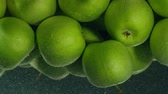 immerse : Green apples fall down in water against black background, super slow motion