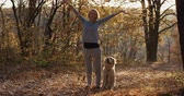 socialisation : Young woman with her dog retriever tossing up leaves in autumn forest park