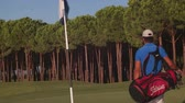 golfe : young golf player with beard walking and carrying bag on course during sunset and sun flare at summer game golfing Vídeos