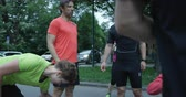 visto : Group of runners seen from behind, jogging together in city park