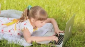 campus : School girl on the grass behind the laptop Stock Footage