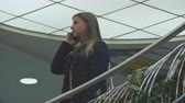 coat : Young blonde girl talking on the phone in a coat. Shopping center.