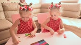 sister : Two cute little twin sisters together are engaged in modeling with multi-colored plasticine. Stock Footage