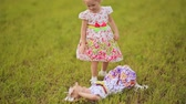 sister : Two cute sisters twins frolicking on a green meadow in summer day. Falling on the grass, laughing and hugging.