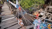 pântano : Coron, Philippines - January 5, 2018: The way of life of children and families in the Filipino slums. Poverty. Children on unsafe wooden bridges from planks on high water. Philippines.